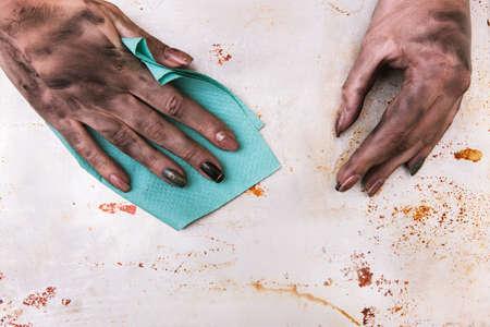 低賃金の仕事と低スキルの職業。汚れた女性はタオルで表面を掃除する 写真素材