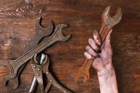 Female repairer. Woman hand holding a spanner and other tools lay on a wooden background. Feminism and emancipation concept
