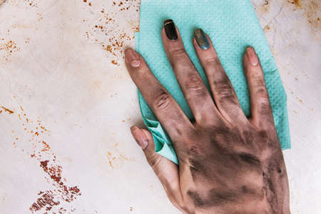 Low-skilled jobs for women. Dirty female hands cleaning surface with a towel