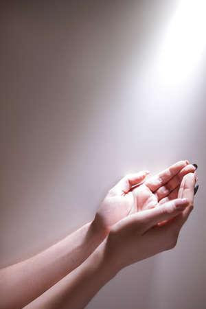 빛나는 빛 아래 손을 받아 하나님의 은혜를받습니다. 열렬한기도 개념