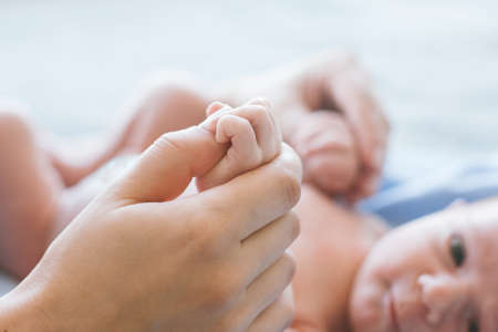 cute newborn baby hold mother by the thumb. happy motherhood. family values. Stock Photo