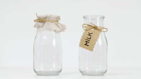 Empty glass milk bottles on white background. Dairy farm quality products concept.