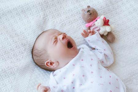 a sleepy newborn is yawning sweetly on the bed. teddy bear toy friend. happy moments of motherhood.