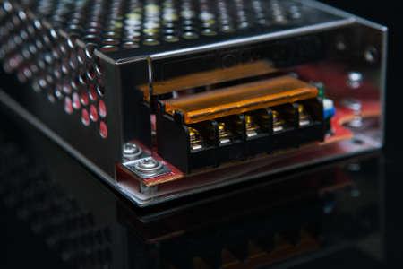 검정색 배경에 변압기 12W입니다. 고전압을 저전압으로 변환합니다. 공학 기술