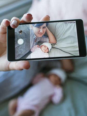 smartphone selfie family newborn mother concept. photo memory. happy motherhood. Фото со стока