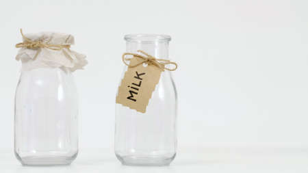 Empty glass milk bottles on white background. Dairy products concept.