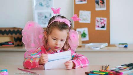 schattig klein meisje kijkt naar foto's op kunstles. schattige prinses. levensstijl van getalenteerde mensen. Stockfoto