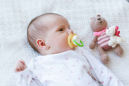 newborn baby laying on bed with his own toy bear. mothers treasure. beginning of life Stock Photo