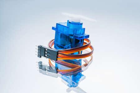 Mikroelektronischer Servomotor auf weißem Hintergrund. Komponente zur Steuerung von Robotern und funkgesteuertem Spielzeug Standard-Bild