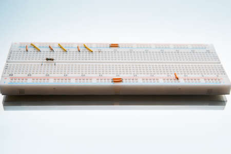 solderless circuit breadboard on white background. experiments with electronics. designing prototypes of various devices Stock Photo