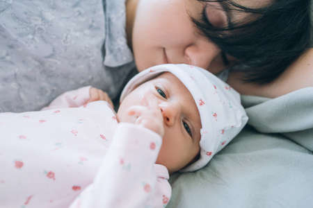 Mom with pleasure sniffing her newborn baby. tenderness and love. happy motherhood. Stock Photo