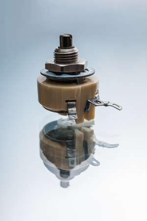 白い背景に可変抵抗。電気回路の電流と電圧を調整する装置 写真素材