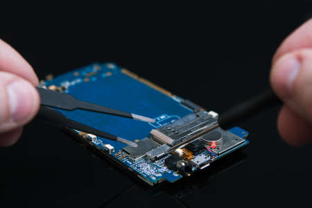 Motherboard repairs on black background. professional mending of smartphones, gadgets and other electronic devices.