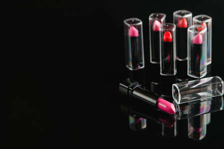 Wide selection of women lipsticks on black background. beauty blog. professional make-up courses. free space concept