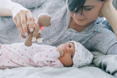 Mère joue avec son bébé nouveau-né un ours en peluche ours famille loisirs heureux. famille amoureuse Banque d'images - 94038566