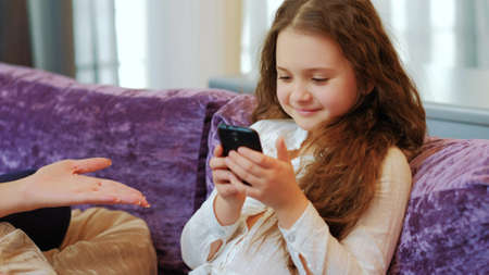 child technology addiction. modern parenting problems. kid upbringing difficulties. little girl looking at her phone. mother wants it back Foto de archivo - 95453500