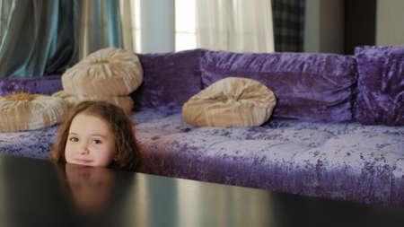 幸せな子供時代。楽しいゲーム時間。かくれんぼや覗き見やピーカブーを再生する子供。テーブルの後ろに隠れている小さな女の子。 写真素材
