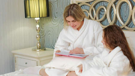 woman reading to her daughter before bedtime