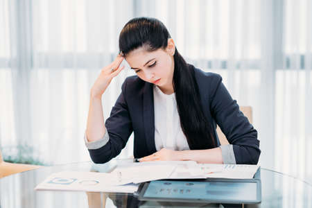 stressed tired business woman. young lady focused on studying report papers and marketing statistics. office workspace Stock Photo