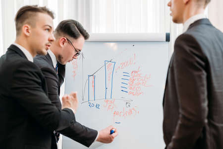 business briefing and goals visualization. company managers writing on the flip chart in office board room