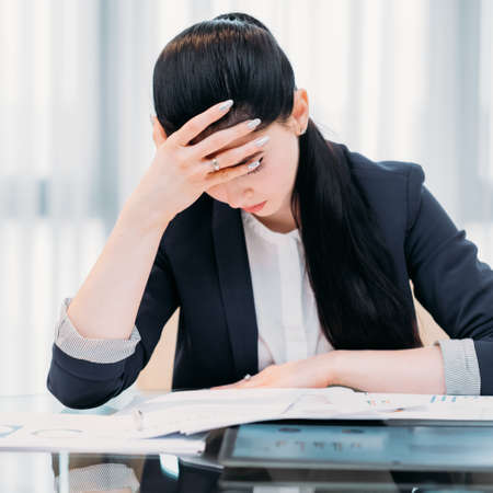 pressure of business. heavy workload. inefficient time management. bad work planning. overworked tired woman sitting at her workplace