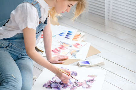 creative art lifestyle. drawing hobby and self expression. young beautiful girl painting a picture at home Stockfoto