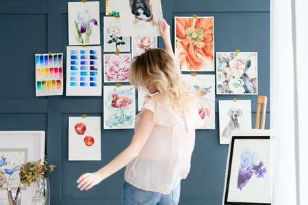 creative art lifestyle. drawing hobby and self expression. painter dancing against the wall with her artwork. watercolor drawing assortment Banque d'images