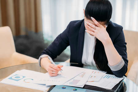 stressed tired business lady. woman overwhelmed with paperwork. girl sitting in office with lots of documents on the desk Stock Photo