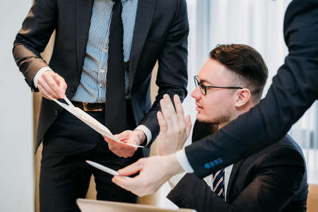 coworkers communication. business man overwhelmed with information from his employees. boss rejecting managers suggestions. busy company director lifestyle. Stock Photo
