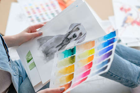 creative art lifestyle. drawing hobby and self expression. woman looking at picture of a dog and color swatches