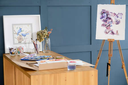 painting art classes. drawings creation. watercolor floral design on an easel. artist accessories tools and ink dyes on the table