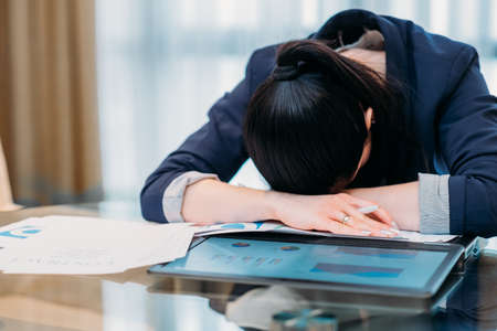 working long hours. deadline. business hardships. overworked tired exhausted woman laid her head on the desk Stock Photo