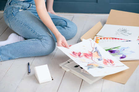 creative leisure. painting hobby. artful personality. painter looking through her drawings