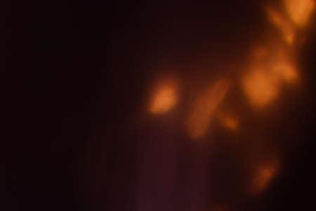 blurred defocused bright light. lens flare. shiny spots. dark background