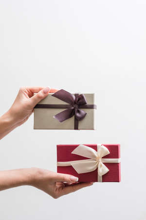 man and woman anniversary or valentines day gifts. presents for him and for her. couple beautiful reward. Woman hand holding two festive packages - feminine and masculine. copy space concept Stok Fotoğraf