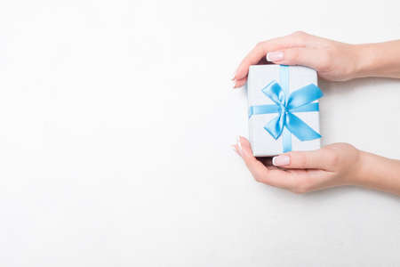small present with blue ribbon bow in woman hands on white background. Sweet reward gift for holiday or birthday. free space concept Stockfoto