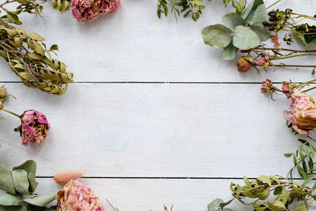 Dried shabby chic flowers and twigs on a white wooden background. Copyspace for text