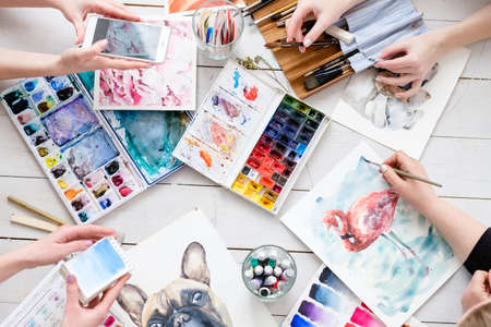 art painting inspiration creativity concept. artist creations. watercolors and drawings color swatches and brushes scattered on the floor