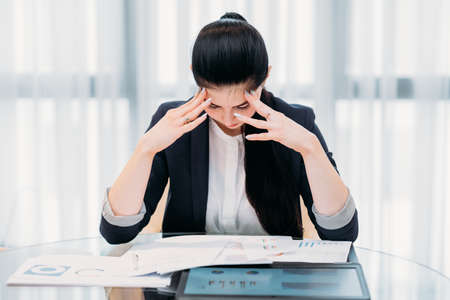 fatigue stress overworked employee. too much information to analyze. young professional woman doing business paperwork in office