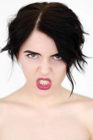 emotion face. furious angry woman in rage baring the teeth. young beautiful brunette girl portrait on white background. Reklamní fotografie