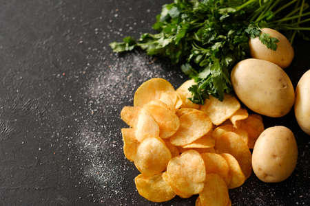 chips preparing. crunchy food crisps cooking. salty ridged fried slices and fresh organic potatoes with green herbs on dark background Stock Photo