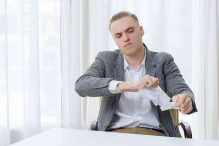 angry disappointed man tearing business papers to pieces. contract loss or work failure concept Stok Fotoğraf