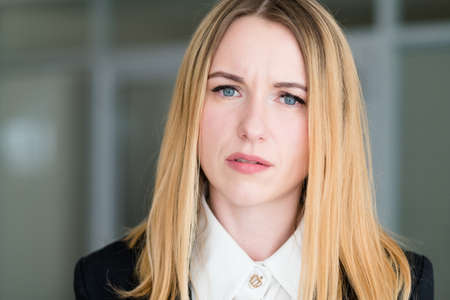 emotion face. woman with a interrogative questioning look. business lady at office workspace. young beautiful blond girl portrait