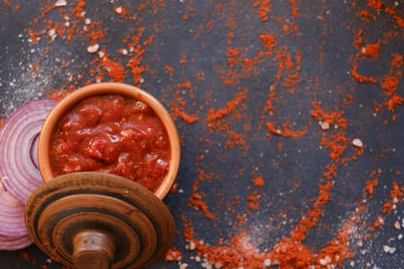 salsa tomato sauce on dark background with scattered flecks of salt and powdered red pepper or paprika. food and culinary condiments. spices mix on rough textured surface. copyspace concept