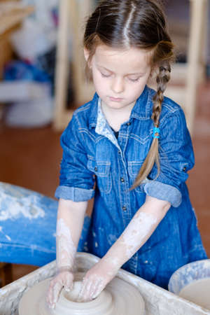 pottery handcraft hobby. little girl forming and shaping a ball of clay on potter wheel Stok Fotoğraf