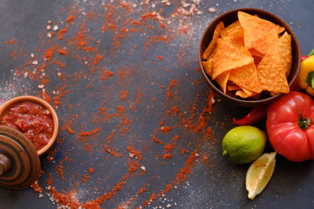 salsa tomato sauce and nacho chips on dark background with flecks of salt and powdered red pepper or paprika.