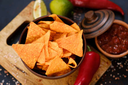 tortilla nacho chips food background. salty spicy crunchy slices in a bowl with  salsa sauce