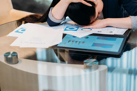 pressure of business. heavy workload. inefficient time management. bad work planning. overworked tired woman laid her head on documents and papers Stock Photo