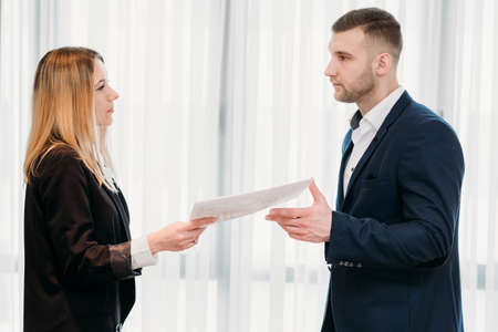 woman handing her letter of resignation to a strict boss. business career change. job quitting. voluntary discharge