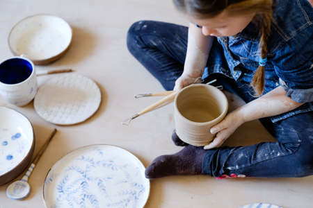 pottery art therapy. creative relaxing leisure. little girl sitting among assortment of handmade plates and crockery Stok Fotoğraf